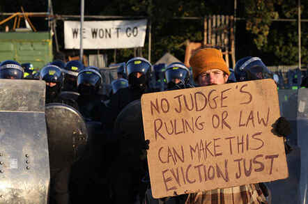 An activist holds up a placard in front of a police line during evictions (Dale Farm, UK, 19 10 2011)(Peter Macdiarmid-Getty Images)